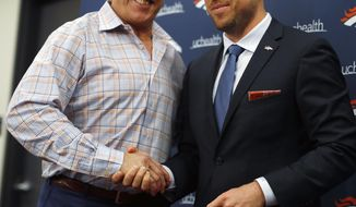 FILE - In this March 16, 2018, file photo, Denver Broncos general manager John Elway, left, shakes hands with Case Keenum during a news conference to introduce him as the new starting quarterback of the Broncos at the team's headquarters, in Englewood, Colo. Count Keenum among those who were stunned by Elway's decision to replace him with Joe Flacco after just one season as the Broncos' starting quarterback. (AP Photo/David Zalubowski, File)