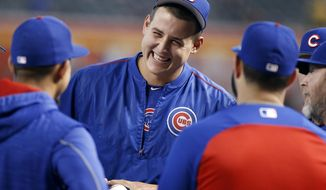 FILE - In this Aug. 12, 2017, file photo, Chicago Cubs' Anthony Rizzo, center, laughs as he talks with teammates before a baseball game against the Arizona Diamondbacks, in Phoenix. For Rizzo, spring training sure has a different feel this year. The three-time All-Star showed up cracking jokes and slinging one-liners as he set out to help the Chicago Cubs bounce back from a disappointing finish last season.(AP Photo/Ralph Freso, File)