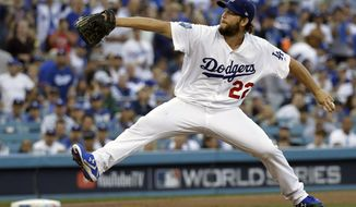 """FILE - In this Oct. 28, 2018, file photo, Los Angeles Dodgers pitcher Clayton Kershaw winds up during the first inning in Game 5 of the World Series baseball game against the Boston Red Sox in Los Angeles. Kershaw has been shut down indefinitely because manager Dave Roberts says the Dodgers ace """"didn't feel right"""" after two discouraging outings on the mound. Kershaw worked out indoors Friday, Feb. 22, 2019, at Camelback Ranch, but did not play catch.  (AP Photo/David J. Phillip, File)"""
