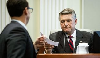 Josh Lawson, chief counsel for the state Board of Elections and Ethics Enforcement, left, hands Mark Harris, Republican candidate in North Carolina's 9th congressional race, a document during the fourth day of a public evidentiary hearing on the 9th congressional district voting irregularities investigation Thursday, Feb. 21, 2019, at the North Carolina State Bar in Raleigh, N.C. (Travis Long/The News & Observer via AP, Pool)
