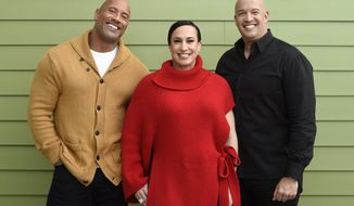 "Dwayne Johnson, left, and Dany Garcia, center, co-founders and co-CEOs of Seven Bucks Productions, and her brother Hiram Garcia, the company's president of production, pose together during the 2019 Sundance Film Festival, Monday, Jan. 28, 2019, in Park City, Utah. Johnson put on his independent film producer hat to make his latest film, ""Fighting With My Family.""  (Photo by Chris Pizzello/Invision/AP)"