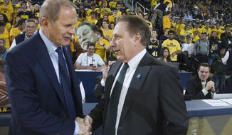 FILE - In this Feb. 7, 2017, file photo, Michigan head coach John Beilein, left, shakes hands with Michigan State head coach Tom Izzo before an NCAA college basketball game in Ann Arbor, Mich. Izzo and Beilein are friendly rivals, whose highly ranked teams will play for the first time this season on Sunday, Feb. 24, 2019, at Crisler Arena. As much as Beilein and Izzo genuinely like and respect each other, the highly competitive coaches want to win. (AP Photo/Tony Ding, File)