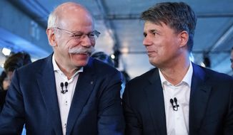 BMW CEO Harald Krueger, right, and Mercedes-Benz CEO Dieter Zetsche of Daimler, left, sit together at a press conference in Berlin, Germany, Friday, Feb. 22, 2019. Automakers Daimler and BMW are formally launching their joint venture in services that make it possible to use their cars without necessarily owning one. (Bernd von Jutrczenka/dpa via AP)