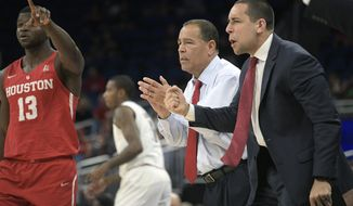 FILE - In this March 11, 2018, file photo, Houston head coach Kelvin Sampson and assistant coach Kellen Sampson, right, celebrate after a score during the first half of an NCAA college basketball championship game against Cincinnati, at the American Athletic Conference tournament, in Orlando, Fla. The entire team piles into coach Sampson's house before each home game to prepare for the next opponent, eat his wife Karen's delicious homemade chocolate chip cookies and bond like a family. The routine is something Sampson and his players agree has created an environment of closeness and trust that is an integral ingredient in the ninth-ranked Cougars' success this season. (AP Photo/Phelan M. Ebenhack, File)