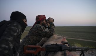 In this Tuesday, Feb. 19, 2019, file photo, U.S.-backed Syrian Democratic Forces fighters watch as an airstrike hits territory still held by Islamic State militants in the desert outside Baghouz, Syria. (AP Photo/Felipe Dana, File)