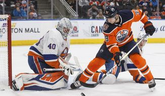 New York Islanders goalie Robin Lehner (40) makes a save against Edmonton Oilers' Alex Chiasson (39) as Islanders' Scott Mayfield (24) tries to defend during second-period NHL hockey game action in Edmonton, Alberta, Thursday, Feb. 21, 2019. (Jason Franson/The Canadian Press via AP)
