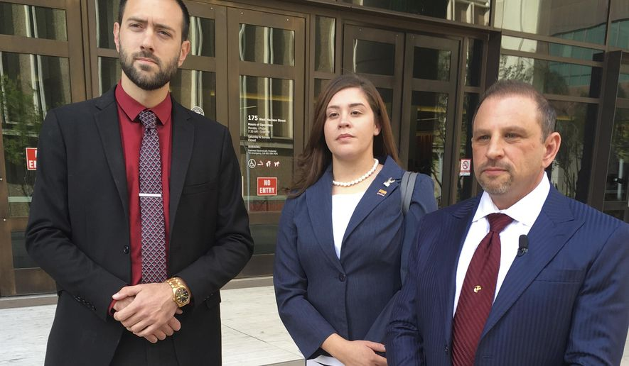 FILE - In this March 29, 2018 file photo, 32-year-old Tahnee Gonzales stands next to her attorneys Marc Victor, right, and Andrew Marcantel, left, outside of a courthouse in Phoenix, Ariz. A new trial date of April 25, 2019 has been set for Gonzales who was captured on video making derogatory comments about Muslims at a Tempe mosque. Gonzales pleaded not guilty to burglary and other charges stemming from her March 4 trip to the mosque. (AP Photo/Jacques Billeaud, File)