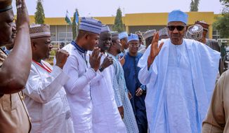 In this photo released by the Nigeria State House, Nigeria's incumbent President Muhammadu Buhari, of the All Progressives Congress party, right, greets supporters as he departs from Daura, Nigeria, bound for Abuja, following the postponement of presidential elections, Saturday, Feb. 16, 2019. Nigeria's presidential candidates on Saturday condemned the last -minute decision to delay the presidential election until Feb. 23. (Bayo Omoboriowo/Nigeria State House via AP)