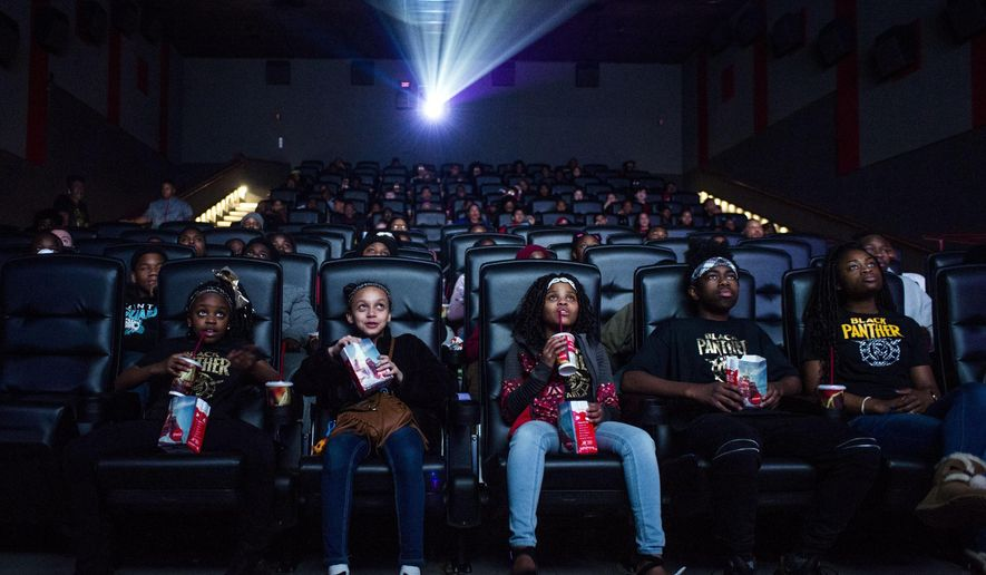 """FILE - In this Feb. 19, 2018, file photo, Mari Copeny, third from left, watches a free screening of the film """"Black Panther"""" with more than 150 children, after she raised $16,000 to provide free tickets in Flint Township, Mich. Streaming services are starting to catch up on getting the latest movies quickly, yet they are no match for the main attraction of movie theaters: no distractions from Facebook, online chats, household chores and what not. (Jake May /The Flint Journal-MLive.com via AP, File)"""