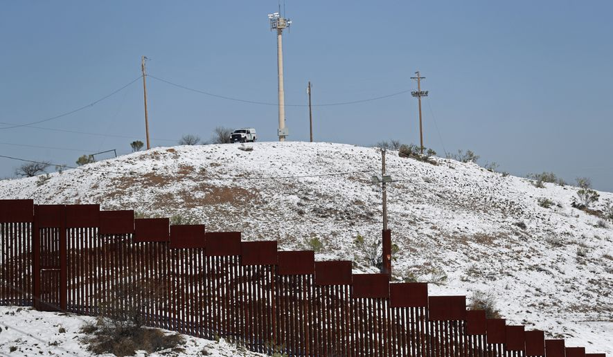 A US Border Patrol truck stands at the top of a snow capped hill overlooking the U.S. Mexico border wall in Nogales, Ariz., after a heavy snowfall, Saturday, Feb. 23, 2019, as seen from Nogales, Mexico. A winter storm dumped record-breaking amounts of snow in Arizona as well as in the northern Mexican city of Nogales. (AP Photo/Dario Lopez-Mills)