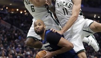 Minnesota Timberwolves' Taj Gibson, bottom, is fouled on a shot-attempt while defended by Milwaukee Bucks' Brook Lopez (11) and Eric Bledsoe (6) during the first half of an NBA basketball game Saturday, Feb. 23, 2019, in Milwaukee. (AP Photo/Aaron Gash)