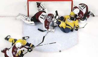 Nashville Predators left wing Filip Forsberg, top center, of Sweden, slides past the net between Colorado Avalanche goaltender Philipp Grubauer (31), of Germany, and defenseman Nikita Zadorov (16), of Russia, during the first period of an NHL hockey game Saturday, Feb. 23, 2019, in Nashville, Tenn. (AP Photo/Mark Humphrey)