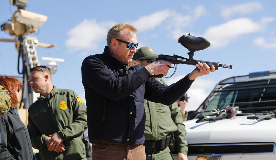 Acting Secretary of Defense Patrick Shanahan, center, fires a modified painted ball gun during a tour of the US-Mexico border at Santa Teresa Station in Sunland Park, N.M., Saturday, Feb. 23, 2019. Top defense officials toured sections of the U.S.-Mexico border Saturday to see how the military could reinforce efforts to block drug smuggling and other illegal activity, as the Pentagon weighs diverting billions of dollars for President Donald Trump's border wall. (AP Photo/Pablo Martinez Monsivais)