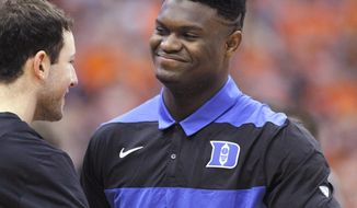Duke's Zion Williamson, right, is greeted by a teammate on the court before the team's NCAA college basketball game against Syracuse in Syracuse, N.Y., Saturday, Feb. 23, 2019. (AP Photo/Nick Lisi)