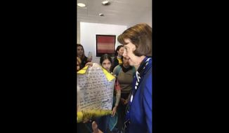 In this image from video provided by Morissa Zuckerman, U.S. Sen. Dianne Feinstein, D-Calif., speaks with a group of students who wanted to discuss the Green New Deal, an ambitious Democrat plan to shift the U.S. economy from fossil fuels and to renewable sources such as wind and solar power, at her office in San Francisco. The students are members of Sunrise Movement, an activist group that encourages children to combat climate change. (Morissa Zuckerman via AP)