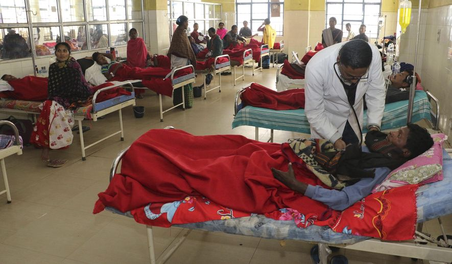 A doctor attends to a victim, who had consumed bootleg liquor, at a hospital in Jorhat in northeastern state of Assam, India, Saturday, Feb. 23, 2019. At least 84 people have died and another 200 have been hospitalized after drinking tainted liquor in two separate incidents in India's remote northeast, authorities said on Saturday. ( AP Photo)