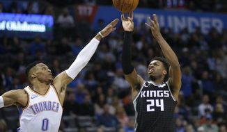 Sacramento Kings guard Buddy Hield (24) shoots in front of Oklahoma City Thunder guard Russell Westbrook (0) during the first half of an NBA basketball game in Oklahoma City, Saturday, Feb. 23, 2019. (AP Photo/Sue Ogrocki)