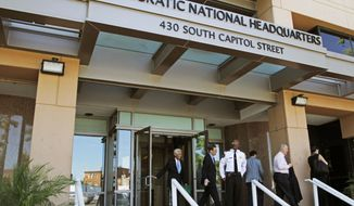 In this June 14, 2016 file photo, people stand outside the Democratic National Committee headquarters in Washington. Hackers tried to break into DNC inboxes in March 2016 and intensified their efforts in early April. (AP Photo/Paul Holston, File)