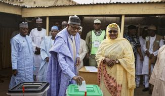 Nigeria's President Muhammadu Buhari casts his vote, accompanied by his wife Aisha, in his hometown of Daura, in northern Nigeria Saturday, Feb. 23, 2019. Nigerians are going to the polls for a presidential election Saturday, one week after a surprise delay for Africa's largest democracy. (AP Photo/Ben Curtis)