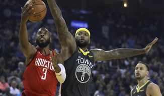 Houston Rockets' Chris Paul, left, lays up a shot past Golden State Warriors' DeMarcus Cousins, center, in the first half of an NBA basketball game Saturday, Feb. 23, 2019, in Oakland, Calif. (AP Photo/Ben Margot)