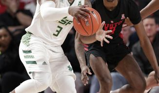 South Florida guard LaQuincy Rideau, left, looks to pass the ball as Houston guard Dejon Jarreau, right, during the second half of an NCAA college basketball game Saturday, Feb. 23, 2019, in Houston. (AP Photo/Michael Wyke)