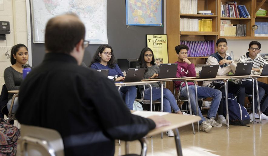 Stuart Wexler leads his Advanced Placement government class in a discussion at Hightstown High School in Hightstown, N.J., Tuesday, Feb. 19, 2019. The high school students set their sights on an ambitious goal _ federal legislation to create a national archive of documents involving decades of unsolved civil rights cases. Students at a New Jersey school had worked on it for years. Now, all they needed was President Donald Trump's signature. But if he didn't act in time, the bill would die. The students took to social media and enlisted the aid of a new senator from Alabama. It worked: Trump signed and it's now law. (AP Photo/Seth Wenig)