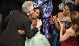 "Yalitza Aparicio, right, congratulates Alfonso Cuaron in the audience as he is announced the winner of the award for best cinematography for ""Roma"" at the Oscars on Sunday, Feb. 24, 2019, at the Dolby Theatre in Los Angeles. (Photo by Chris Pizzello/Invision/AP)"