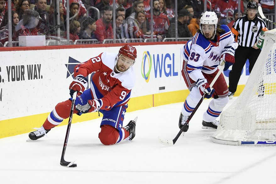 Washington Capitals center Evgeny Kuznetsov (92), of Russia, reaches for the puck against New York Rangers center Mika Zibanejad (93) during the first period of an NHL hockey game, Sunday, Feb. 24, 2019, in Washington. (AP Photo/Nick Wass) ** FILE **