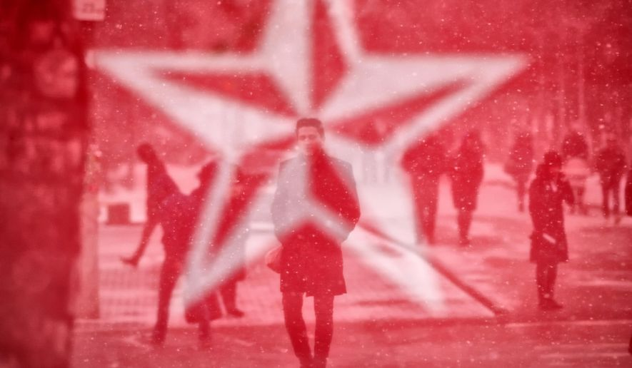 """Seen through the mesh covering an electoral advertising point of the Socialits' Party, people walk in Chisinau, Moldova, Saturday, Feb. 23, 2019, a day before the country holds parliamentary elections. Moldova's President Igor Dodon expressed, in an interview with the Associated Press, concern of """"massive protests"""" in case of suspicions of fraud in the upcoming parliamentary elections. (AP Photo/Vadim Ghirda)"""