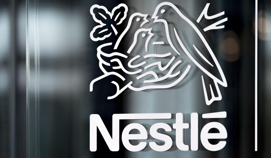 FILE - In this Thursday, Feb. 14, 2019, file photo, Nestle's logo is displayed on a window, during the 2018 full-year results press conference of the food and drinks giant Nestle, in Vevey. A report published Monday by the non-governmental group CDP found consumer goods giants are working to lower their carbon emissions, prepare for the effects of global warming and respond to growing environmental consciousness among customers. (Laurent Gillieron/Keystone via AP, File)