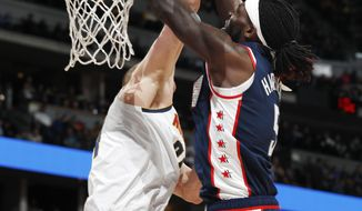 Los Angeles Clippers forward Montrezl Harrell, front, dunks the ball for a basket over Denver Nuggets forward Mason Plumlee in the first half of an NBA basketball game Sunday, Feb. 24, 2019, in Denver. (AP Photo/David Zalubowski)