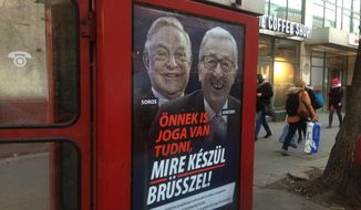 """FILE - In this Feb. 19, 2019 file photo, a phone box displays a billboard showing Hungarian-American financier George Soros and EU Commission President Jean-Claude Juncker above the caption """"You have a right to know what Brussels is preparing to do!"""", in Budapest, Hungary. Battle lines are drawn between anti-EU populist forces and traditional parties at the beginning of a three-month election campaign that could turn into a tipping point in postwar European history. The May 2019 EU elections has already produced unprecedented abrasive campaigning. (AP Photo/Pablo Gorondi, File)"""