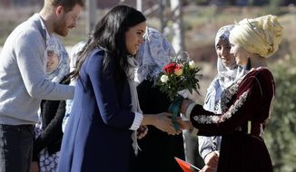Britain's Prince Harry and Meghan, Duchess of Sussex are greeted as they arrive for a visit to an 'Education for All' boarding house in Asni Town in Morocco, Sunday, Feb. 24, 2019. The Duke and Duchess of Sussex are on a three day visit to the country. (AP Photo/Kirsty Wigglesworth)