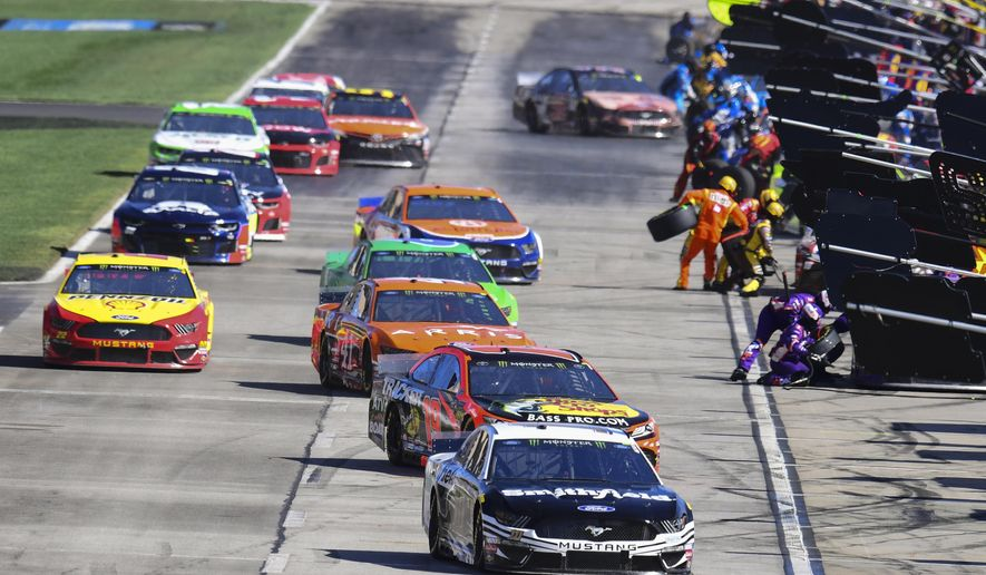 Aric Almirola (10) is followed by Martin Truex Jr. (19) as they and others pit during a NASCAR Monster Energy NASCAR Cup Series auto race at Atlanta Motor Speedway, Sunday, Feb. 24, 2019, in Hampton, Ga. (AP Photo/Scott Cunningham)
