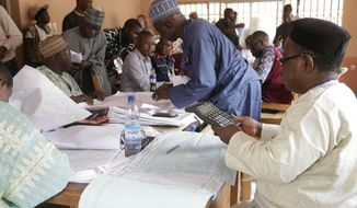Electoral officials compile voting results at a collation center in Yola, n Nigeria, Sunday, Feb. 24, 2019. Vote counting continued Sunday as Nigerians awaited the outcome of a presidential poll seen as a tight race between the president and a former vice president. (AP Photo/Sunday Alamba)