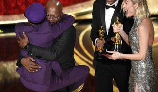 """Samuel L. Jackson, center left, embraces Spike Lee, winner of the award for best adapted screenplay for """"BlacKkKlansman"""" as Brie Larson, right, looks on, at the Oscars on Sunday, Feb. 24, 2019, at the Dolby Theatre in Los Angeles. (Photo by Chris Pizzello/Invision/AP)"""
