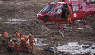 FILE - In this Jan. 28, 2019 file photo, firefighters prepare a body to be lifted away by a helicopter, after pulling the dead person from the mud days after a dam collapse in Brumadinho, Brazil. The Minas Gerais state government said in a statement Wednesday, Feb. 20, that blood and urine tests conducted on firefighters searching through muddy mine waste for missing people after a dam collapse show high levels of potentially toxic metals. (AP Photo/Leo Correa, File)