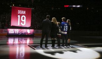 From left to right Shane Doan, left, wife Andrea Doan, children Carson Doan, Josh Doan, and Karys Doan, watch as the Arizona Coyotes retire Shane's jersey during a ceremony prior to an NHL hockey game against the Winnipeg Jets Sunday, Feb. 24, 2019, in Glendale, Ariz. (AP Photo/Ross D. Franklin)