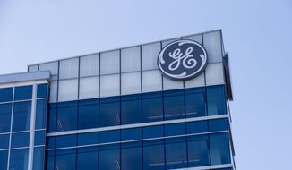 In this Jan. 16, 2018, photo, the General Electric logo is displayed at the top of their Global Operations Center in the Banks development of downtown Cincinnati. (AP Photo/John Minchillo) **FILE**