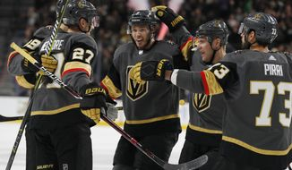 Vegas Golden Knights celebrate after defenseman Shea Theodore (27) scored against the Winnipeg Jets during the second period of an NHL hockey game Friday, Feb. 22, 2019, in Las Vegas. (AP Photo/John Locher)