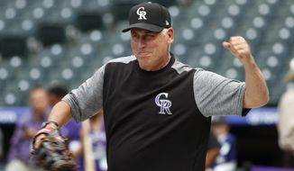FILE - In this Aug. 22, 2018, file photo, Colorado Rockies manager Bud Black jokes with the San Diego Padres television announcers as the Rockies warm up before a baseball game against the Padres, in Denver. The Rockies have agreed to a three-year contract extension with manager Bud Black after he guided the team to back-to-back playoff appearances.His contract runs through the 2022 season, the team announced Monday, Feb. 25, 2019, in Scottsdale, Arizona.(AP Photo/David Zalubowski, File)