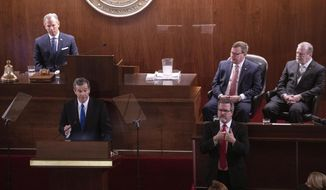 Flanked by Lt. Gov. Dan Forest, left, and House Speaker Tim Moore and Senate Leader Phil Berger, right, Gov. Roy Cooper delivers the biennial State of the State address to a joint session of the General Assembly  in Raleigh, N.C., Monday, Feb. 26, 2019. (Travis Long/The News & Observer via AP)