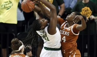 Texas guard Audrey Warren (31) watches as Baylor center Kalani Brown (21) works to take a shot while forward Olamide Aborowa (14) defends in the first half of an NCAA college basketball game in Waco, Texas, Monday, Feb. 25, 2019. (AP Photo/Tony Gutierrez)