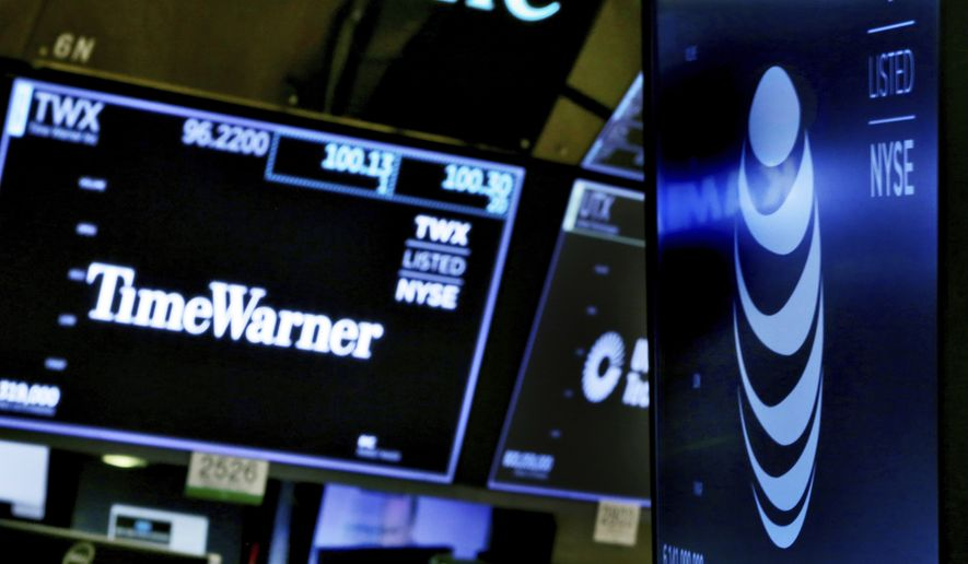 In this June 13, 2018, file photo, the logos for Time Warner and AT&T appear above alternate trading posts on the floor of the New York Stock Exchange.  A federal appeals court has blessed AT&T's takeover of Time Warner, Tuesday, Feb. 26, 2019, defeating the Trump administration by affirming that the $81 billion merger won't harm consumers or competition in the booming pay TV market. (AP Photo/Richard Drew, File)