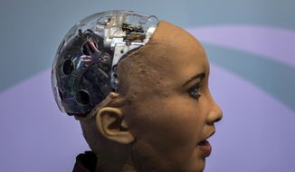 Hanson Robotics' flagship robot Sophia, a lifelike robot powered by artificial intelligence, speaks with visitors, at the Mobile World Congress wireless show, in Barcelona, Spain, Tuesday, Feb. 26, 2019. (AP Photo/Emilio Morenatti) ** FILE **