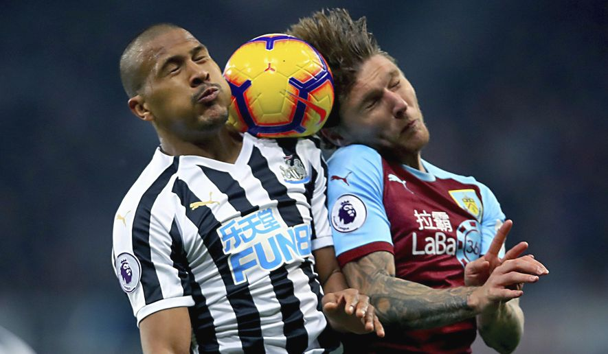 Newcastle United's Salomon Rondon, left and Burnley's Jeff Hendrick battle for the ball in the air, during the English Premier League soccer match between Newcastle and Burnley, at St James' Park, in Newcastle, England, Tuesday, Feb. 26, 2019. (Owen Humphreys/PA via AP)