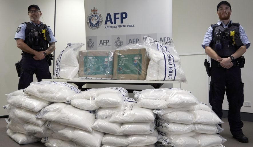 Police guard some of the 1.4 tons of seized ephedrine that is piled up during an Australian Federal Police press conference in Melbourne, Wednesday, Feb. 27, 2019. Australian authorities say they seized chemicals which could have been used to make one ton of methamphetamine and arrested four men in a joint operation with China. (Erik Anderson/AAP Image via AP)