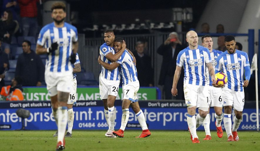 Huddersfield Town's Steve Mounie, back left, celebrates scoring his side's first goal of the game in the 90th minute during the Premier League match at the John Smith's Stadium, Huddersfield, Tuesday February 26, 2019. (Martin Rickett/PA via AP)