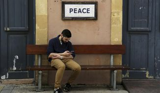 """A man sits by a sign reading 'Peace"""" near from the main Ledra checkpoint that crosses from the south, Greek, to the ,north, Turkish Cypriots, controlled areas in divided capital Nicosia, Cyprus, Tuesday, Feb. 26, 2019. Cypriot President Nicos Anastasiades and breakaway Turkish Cypriot leader Mustafa Akinci they meet today under the U.N to laying the groundwork for a return to reunification negotiations almost two years after the most recent bid to hammer out a peace accord collapse. (AP Photo/Petros Karadjias)"""