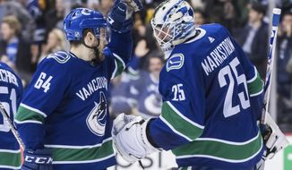 Vancouver Canucks' Tyler Motte, left, and Vancouver Canucks goalie Jacob Markstrom, of Sweden, celebrate after Vancouver defeated the Anaheim Ducks, 4-0, during an NHL hockey game in Vancouver, British Columbia, Monday Feb. 25, 2019. (Darryl Dyck/The Canadian Press via AP)